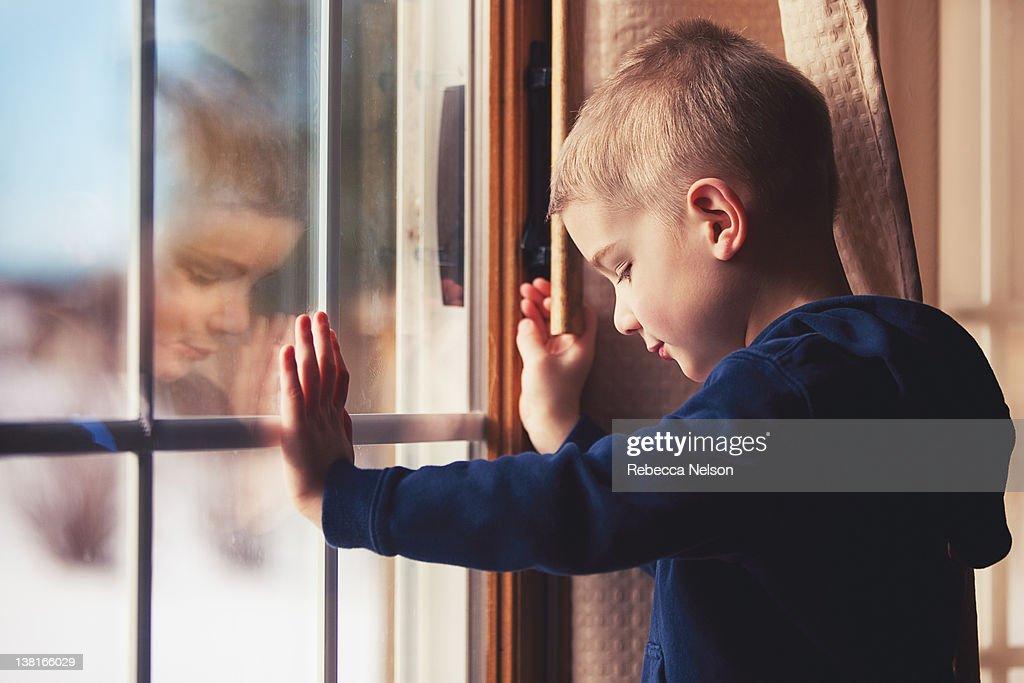 Little boy reflected in glass patio door : Stock Photo