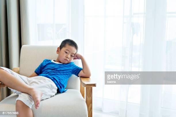 Little boy relaxing in armchair