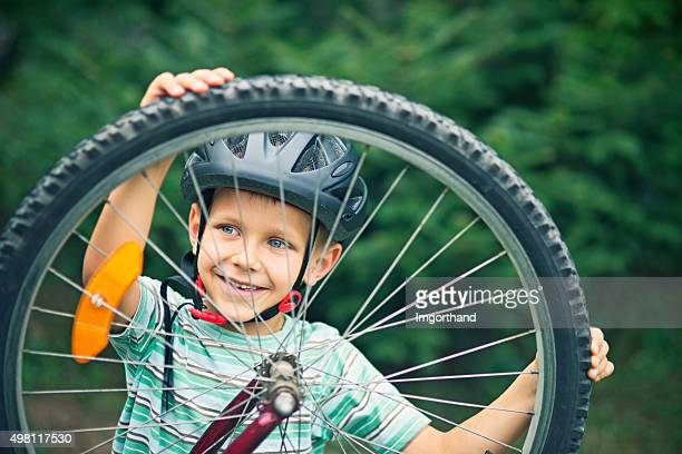 Little boy repairing a bicycle
