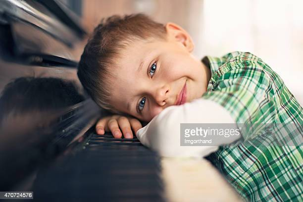 Little boy resting on his piano