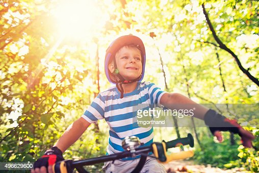 Little boy riding a bicycle in forest