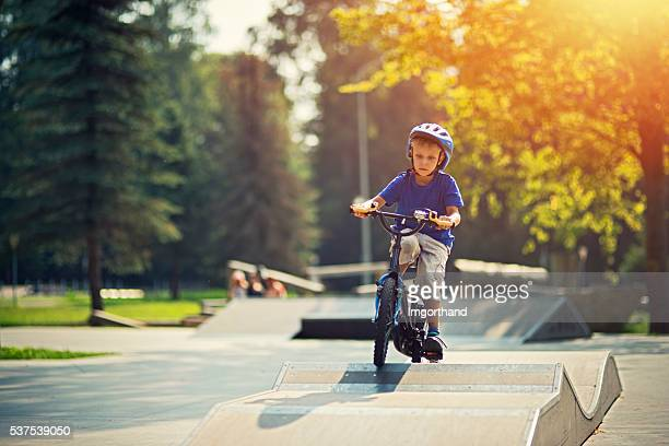 Little boy riding a bicycle on ramp