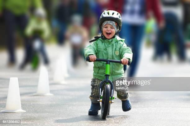 Little boy riding a runbike
