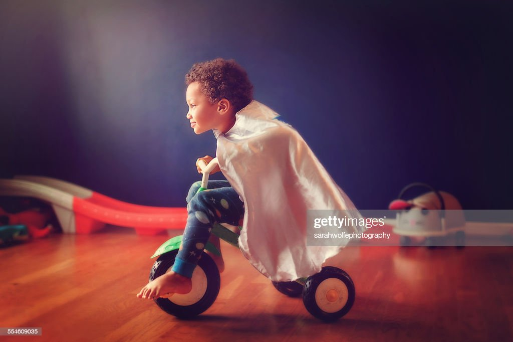 little boy riding a tricycle in a super hero cape