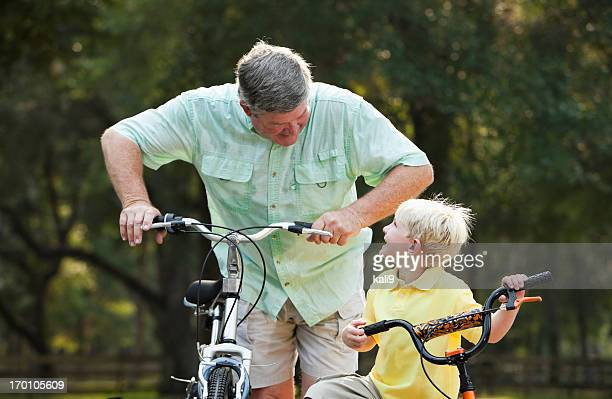 Little boy riding bike with grandfather