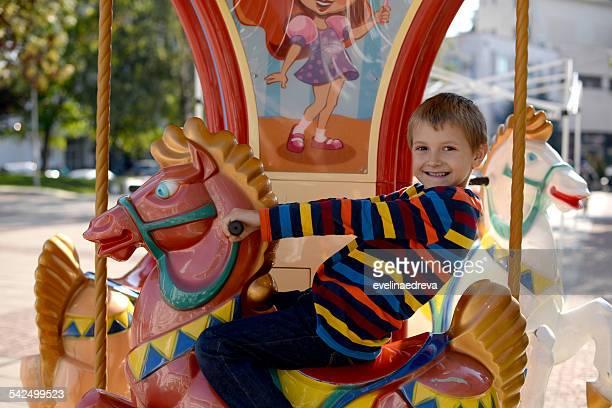 Little boy (6-7) riding carousel horse