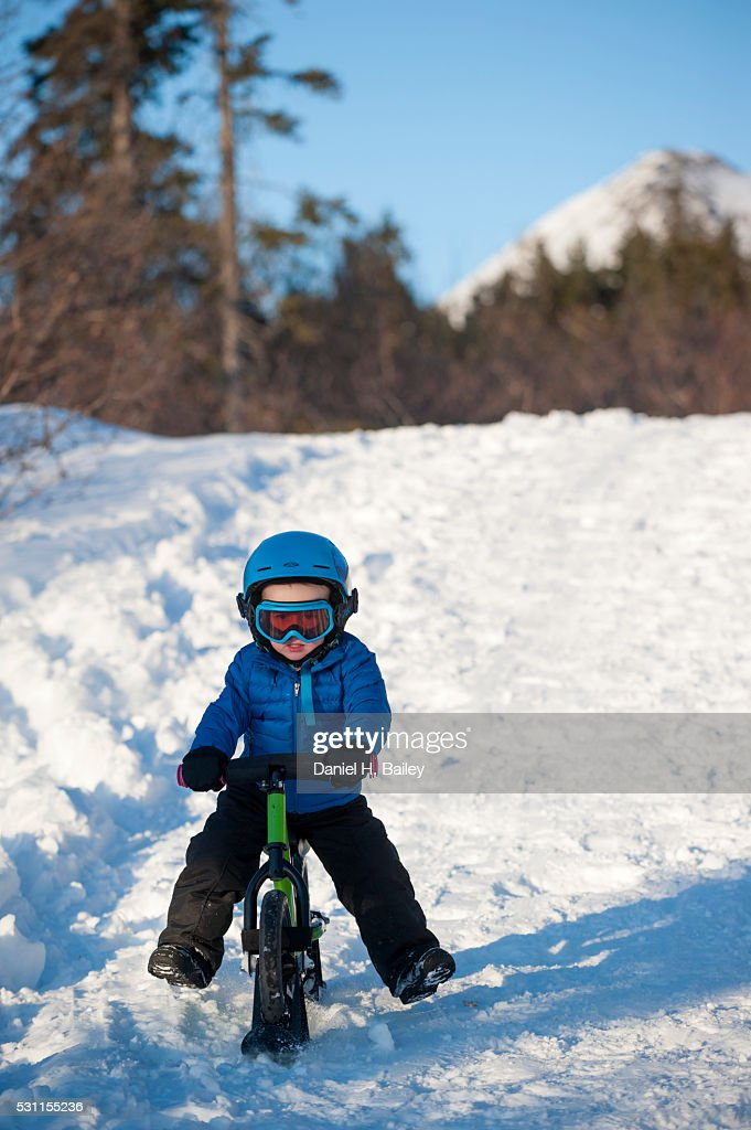 Little Boy Riding His Ski Skoot Bike Down A Snowy Trail Stock