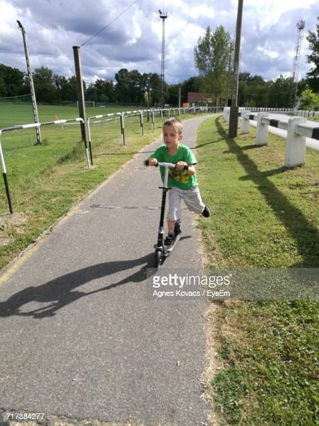 Little Boy Riding Push Scooter On Footpath