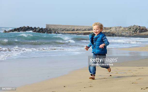 Little boy running along waterfront