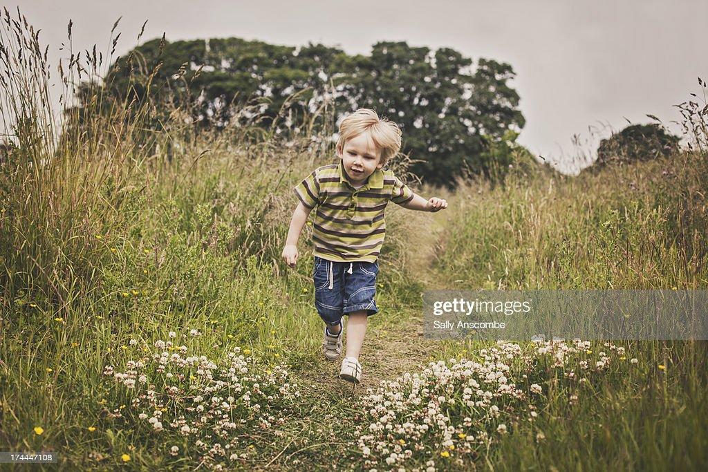 Little boy running through a field : Stock Photo
