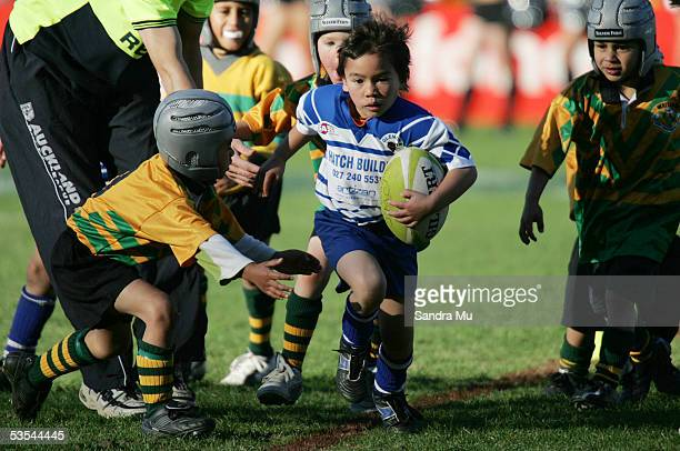 A little boy runs from a tackle during a kids game of league in between the New Zealand Warriors v Brisbane Broncos at Ericsson Stadium in Auckland...