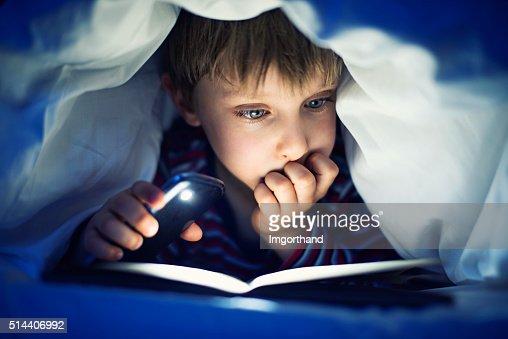 Little boy secretly reading book under sheets