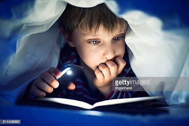 Insgeheim kleiner Junge liest ein Buch unter Bettwäsche