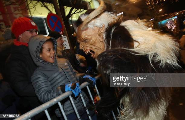 A little boy seems unfazed while confronting a devilish Krampus creature during the annual Krampus parade on Saint Nicholas Day on December 6 2017 in...
