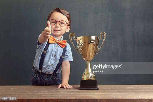 Little boy showing his thumb up with a golden trophy