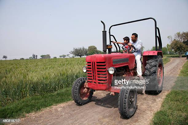 Little boy showing something to father while sitting in tractor at farm