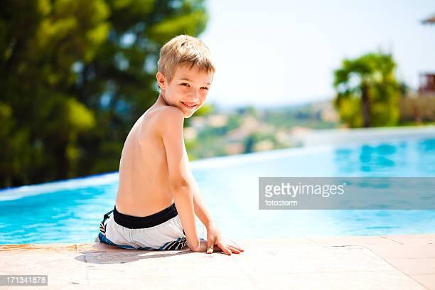 Petit garçon assis au bord de la piscine à débordement