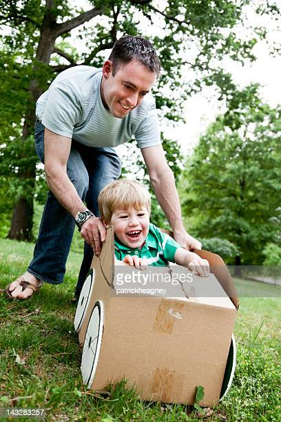 Little boy sitting in a cardboard car and being pushed