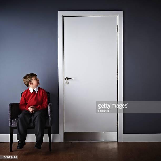 Kleiner Junge sitzt auf der Vorderseite von headmaster Büro