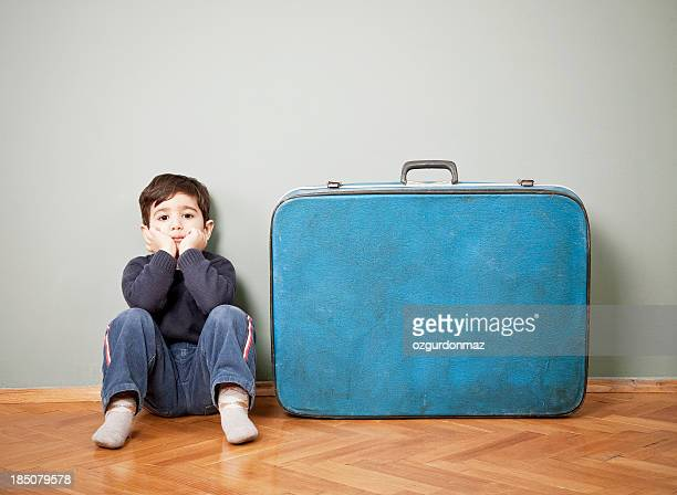 Little boy sitting next to an old suitcase