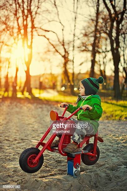 Little boy sitting on a chopper and dreaming about highway