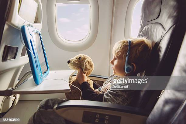 Little boy sitting on an airplane watching something on digital tablet