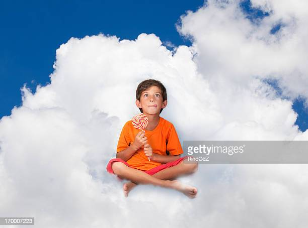 Little Boy Sitting On Cloud With Lollypop