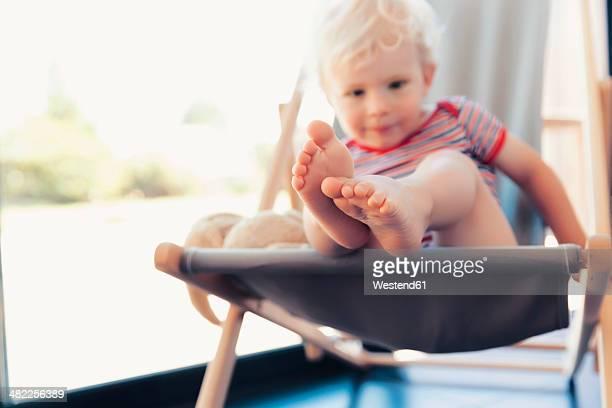 Little boy sitting on deck-chair