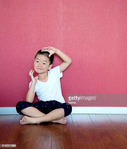 Little boy sitting on floor against wall