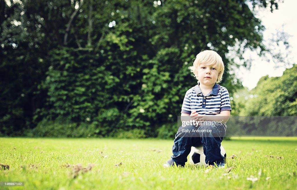 Little boy sitting on football : Stock Photo