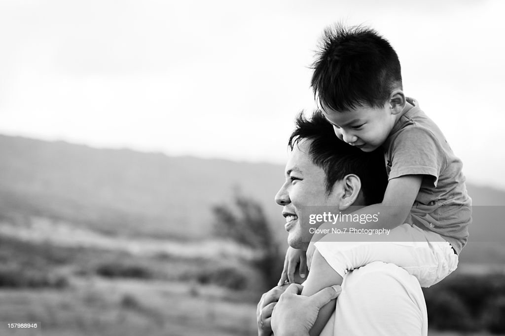 Little boy sitting on his father's shoulders on : Stock Photo