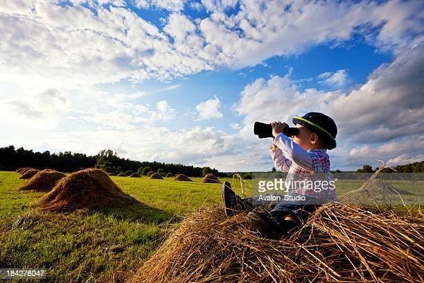Little boy sitting on mounds of hay