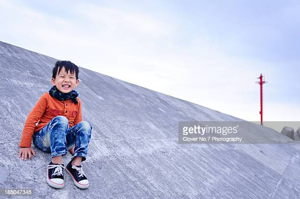 Little boy sitting on the breakwater