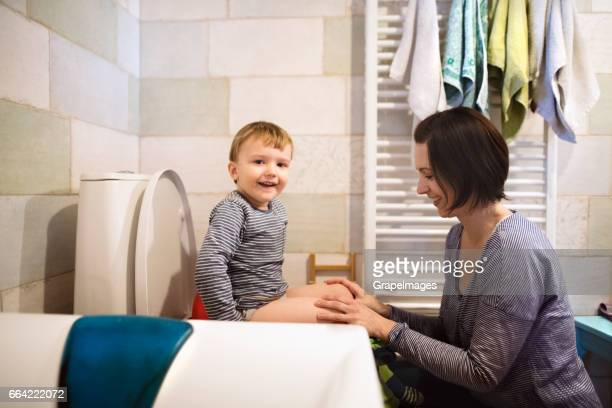Little boy sitting on the toilet, beautiful mother holding him