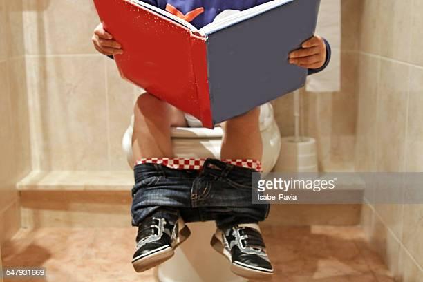 Little boy sitting on toliet reading book