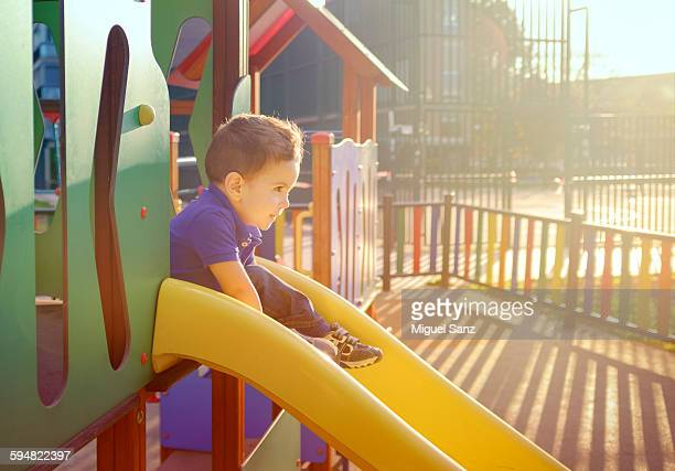 Little boy sliding down a slide at the playground