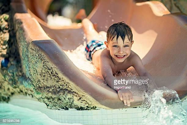 Little boy sliding in water park