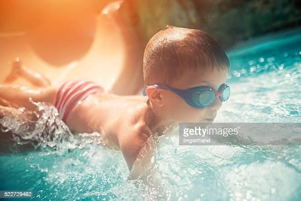 Kleiner Junge in Wasser und Rutschen im Wasserpark