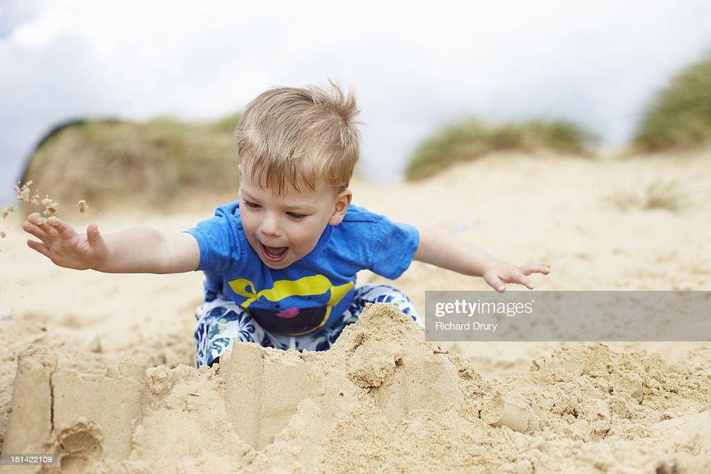 Little boy smashing sandcastles : Stock Photo