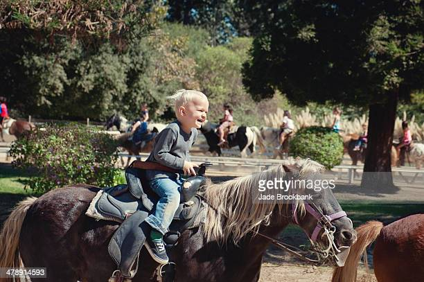 Little boy smiling while riding pony