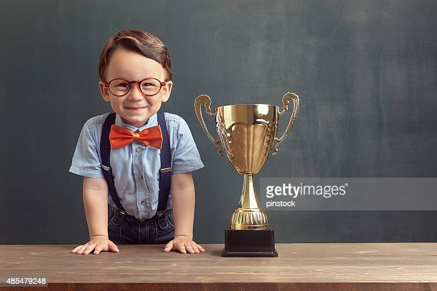 Little boy smiling with a golden trophy