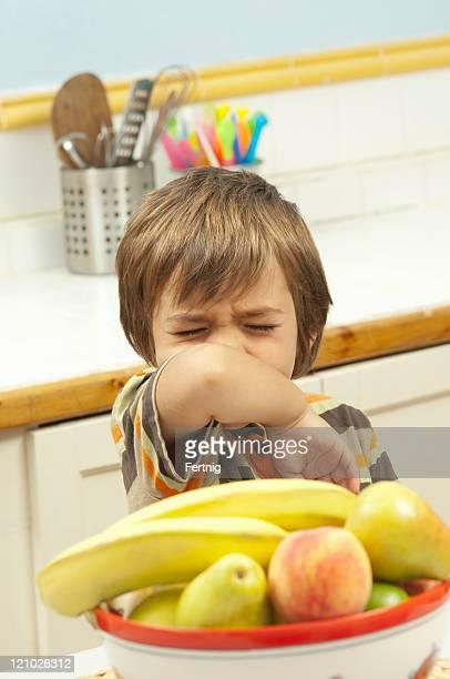 Little boy sneezing into his arm