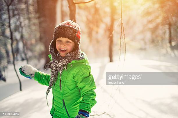 Little boy snowball fight in sunny winter forest