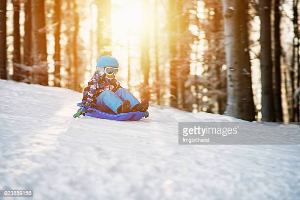 Little boy speeding on his sled in winter forest
