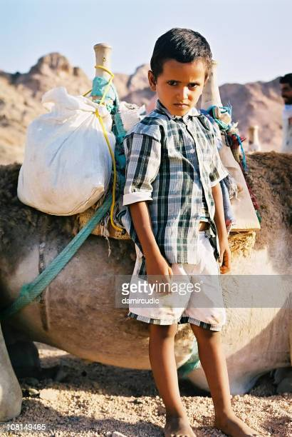 Little Boy Standing in Desert with his Camel