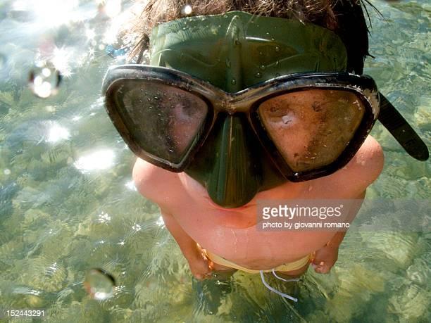 Little boy standing in sea and wearing scuba  mask