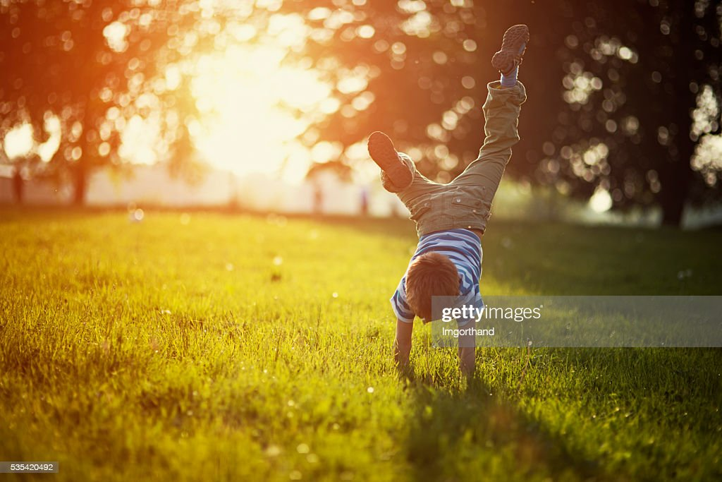 Little boy standing on hands on grass : Stockfoto