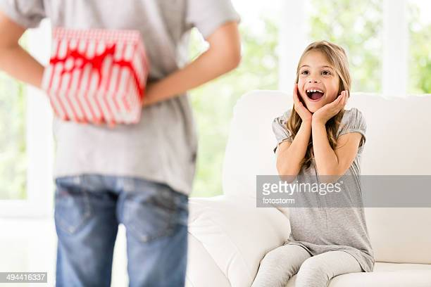 Little boy surprising his sister with a present