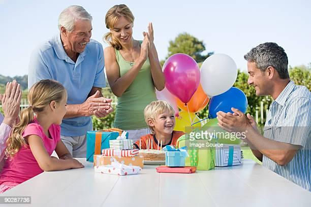 Little boy rodeado de las palmas familia, presenta y coloridos globos