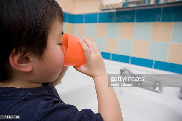 Little boy Taking a Drink in the bathroom
